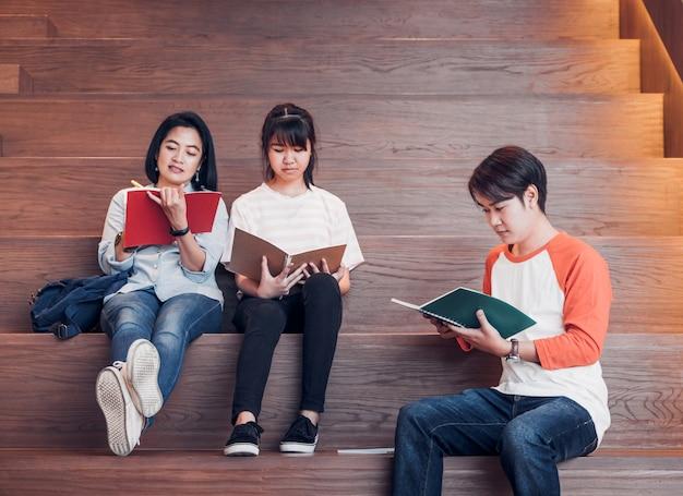 Grupos de estudiantes adolescentes asiáticos que leen el libro juntos en la biblioteca de la escalera de la universidad