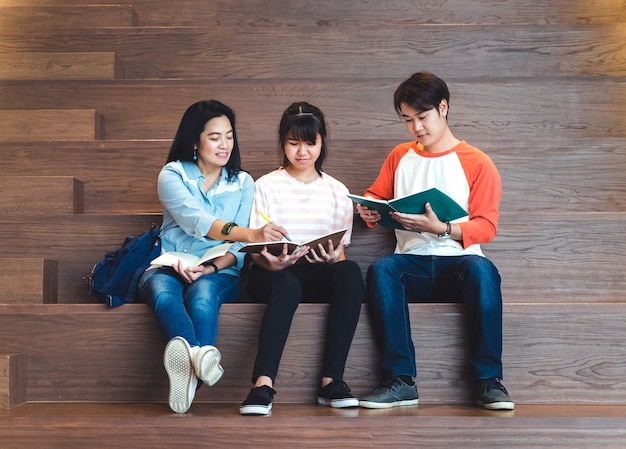 Grupos de estudiantes asiáticos adolescentes que estudian juntos en la biblioteca de la escalera de la universidad