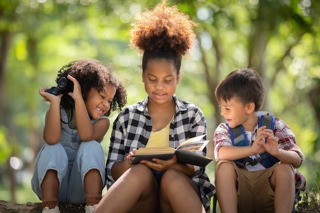 Grupos de niños charlando bajo la sombra de los árboles mientras exploran el bosque
