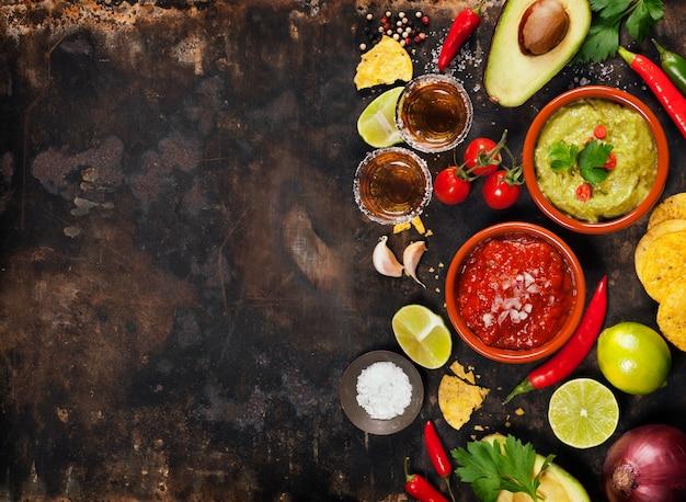 Guacamole verde casero con chips de tortilla, salsa y tequila