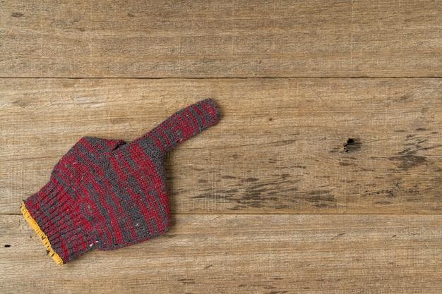 Guante de algodón muestra el signo del dedo índice en la tabla de madera en mal estado.