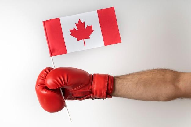 Guante de boxeo con bandera de canadá. el boxeador sostiene la bandera de canadá. fondo blanco.