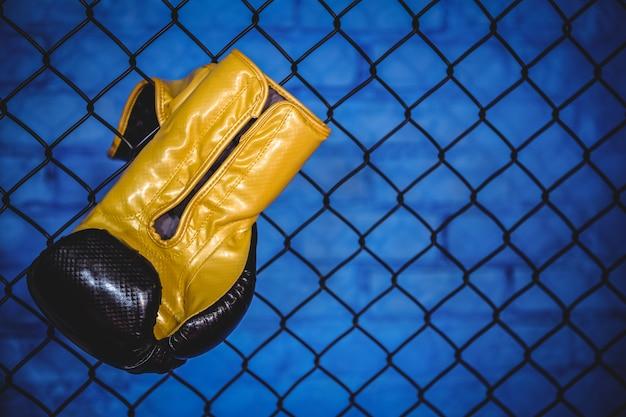 Guante de boxeo colgado en la cerca de malla de alambre