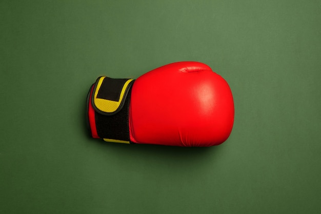 Guante de boxeo rojo y amarillo brillante. equipamiento deportivo profesional aislado en superficie verde. concepto de deporte, actividad, movimiento, estilo de vida saludable, bienestar. colores modernos.