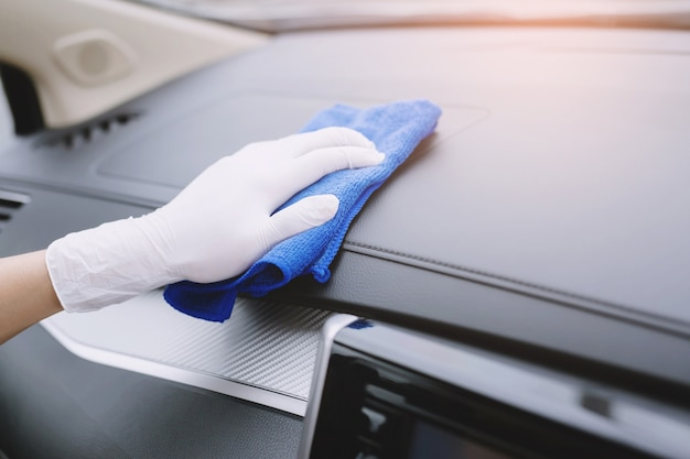 Un guante de mano de trabajador limpiando el volante de la consola del coche con un paño de microfibra, concepto de detalle de lavado de coches.