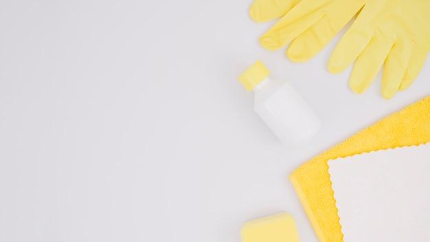 Guantes amarillos; botella; esponja y servilleta aisladas sobre fondo blanco