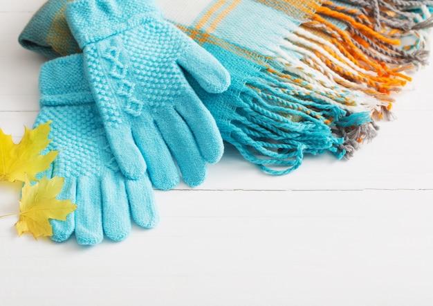 Guantes azules y bufanda sobre fondo blanco de madera