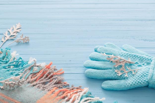 Guantes azules y bufanda sobre fondo de madera