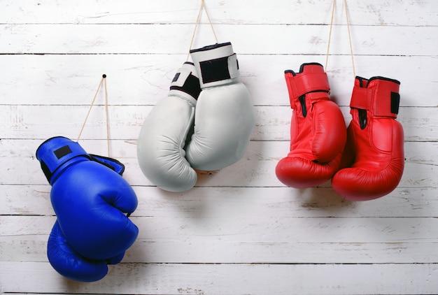 Guantes de boxeo de pared azul, blanco y rojo colgados.
