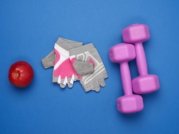 Guantes deportivos, un par de mancuernas moradas y una manzana roja sobre una superficie azul