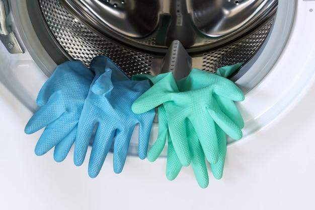 Guantes de goma azules y verdes en una lavadora abierta.