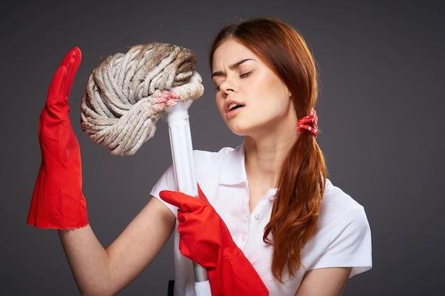 Guantes de goma de mujer bonita trapeador en manos emociones fondo oscuro. foto de alta calidad