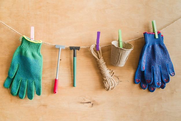 Guantes de jardineria; herramientas; cuerda; macetas de turba colgando de una cuerda con una pinza de ropa contra una pared de madera