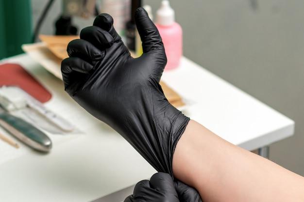 Guantes médicos de látex negro en la mano de la enfermera o esteticista.