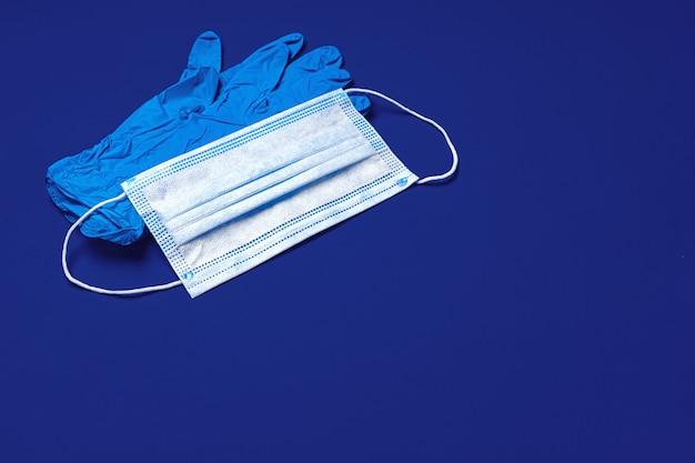 Guantes médicos y mascarilla quirúrgica protectora en azul oscuro