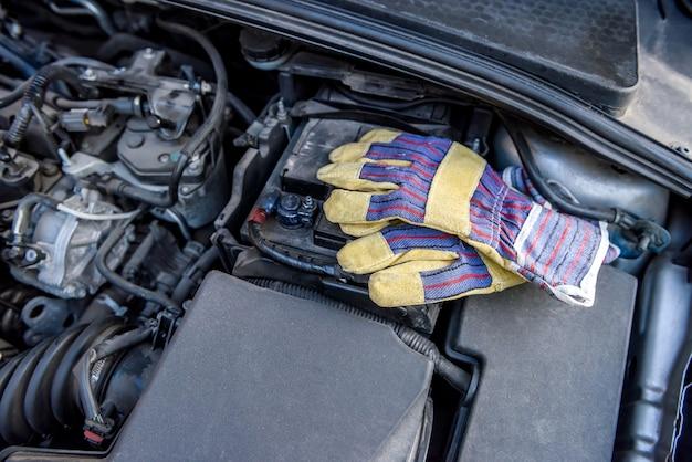 Guantes de protección con llaves en el motor del automóvil