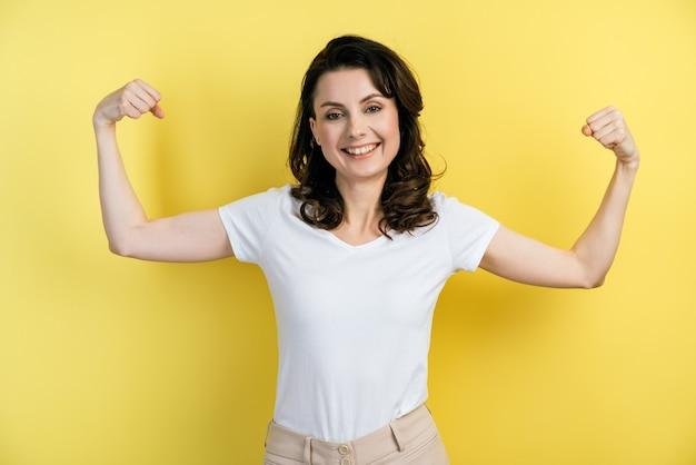 La guapa modelo femenina se mantiene en forma y saludable, levanta los brazos y muestra sus músculos