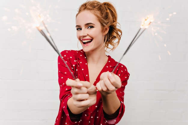 Guapa mujer europea celebrando las vacaciones de invierno con luces de bengala. agradable chica caucásica en pijama rojo sosteniendo bengalas y sonriendo.