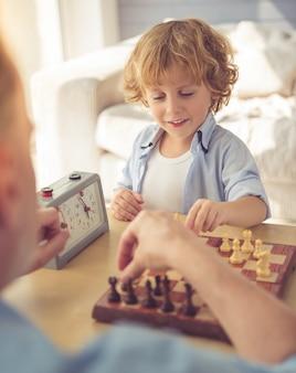 Guapo abuelo y nieto están jugando ajedrez y sonriendo.