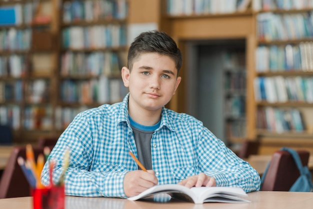 Guapo adolescente haciendo notas en libros de texto