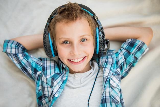 Guapo adolescente pone y escucha música con auriculares