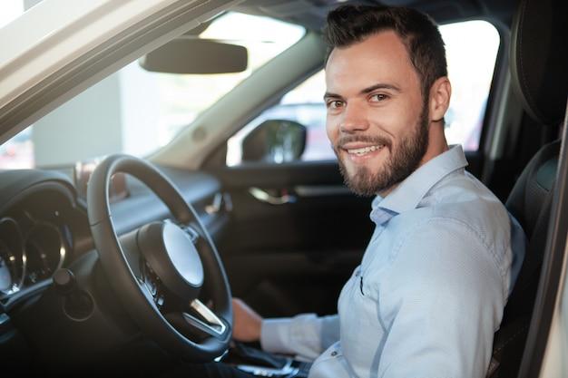 Guapo alegre conductor masculino sonriendo a la cámara, sentado en su automóvil