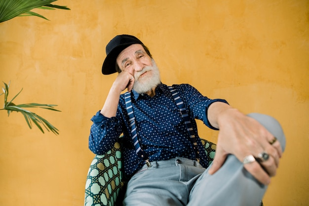 Guapo, alegre, moderno, hombre mayor, con barba bien arreglada, vestido con camisa azul oscuro, tirantes, pantalones grises y gorra hipster negra, sentado en una silla en el estudio frente a la pared amarilla
