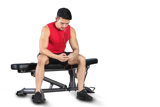 Guapo atlético hombre de deportes escuchando música con auriculares en el gimnasio interior sobre fondo blanco.