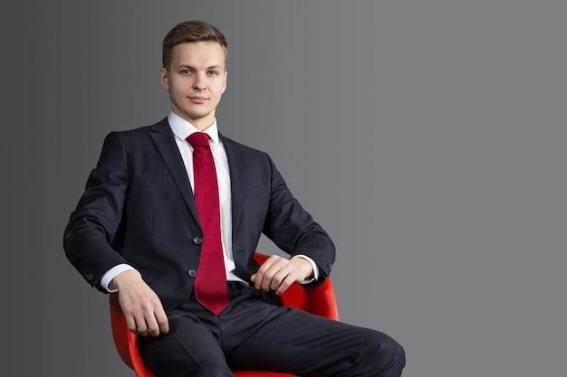 Guapo, atractivo hombre rubio en traje y corbata roja emplazamiento en silla