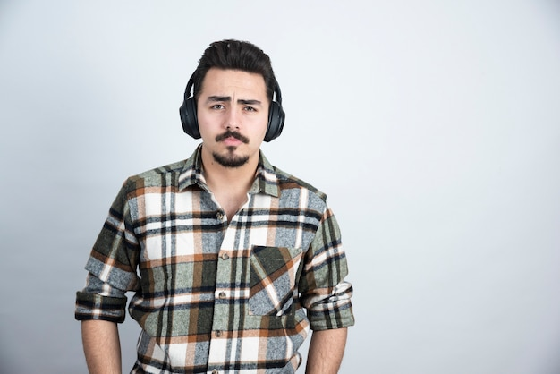 Guapo en auriculares mirando a la cámara sobre una pared blanca.