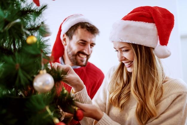 Guapo barbudo sonriente hombre caucásico ayudando a su novia a decorar el abeto. ambos con sombreros de santa en la cabeza. salón interior.