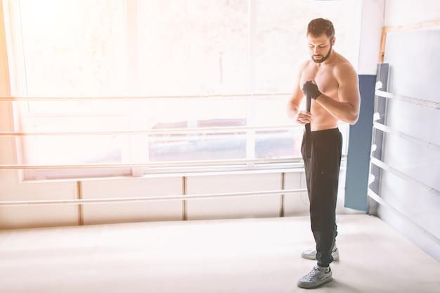 Guapo boxeador barbudo con el torso desnudo envolviendo sus manos, listo para luchar en el club de lucha