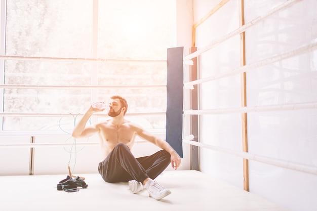 Guapo boxeador barbudo con el torso desnudo está practicando en el club de lucha