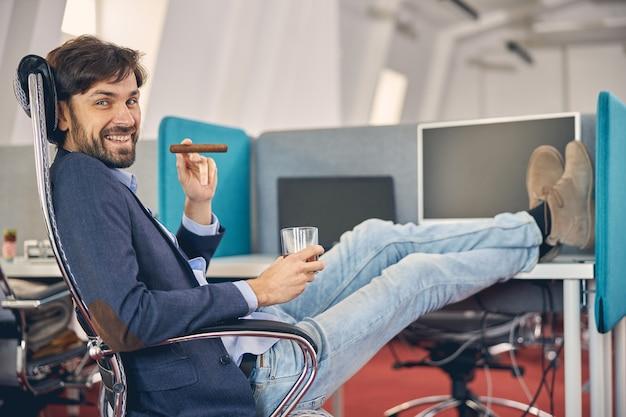 Guapo caballero barbudo mirando a cámara y sonriendo mientras sostiene un vaso de bebida alcohólica y cigarro