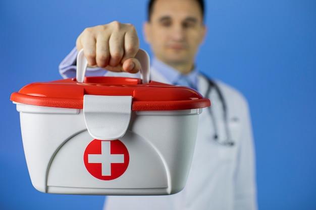 Guapo cabello oscuro 40s doctor masculino tiene kit de ayuda médica de la cruz roja