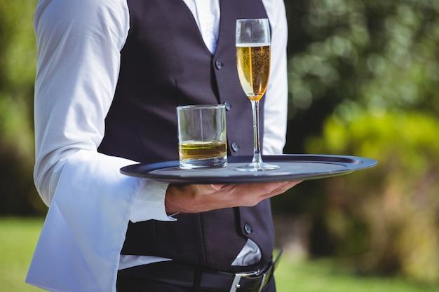 Guapo camarero sosteniendo una bandeja con bebidas