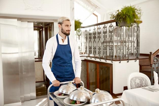 El guapo camarero vestido con el uniforme sirve platos calientes en el restaurante.