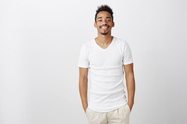 Guapo chico afroamericano sonriente cogidos de la mano en los bolsillos, de pie en ropa casual