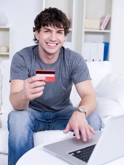 Guapo chico sonriente feliz con tarjeta de crédito y usando laptop - en interiores