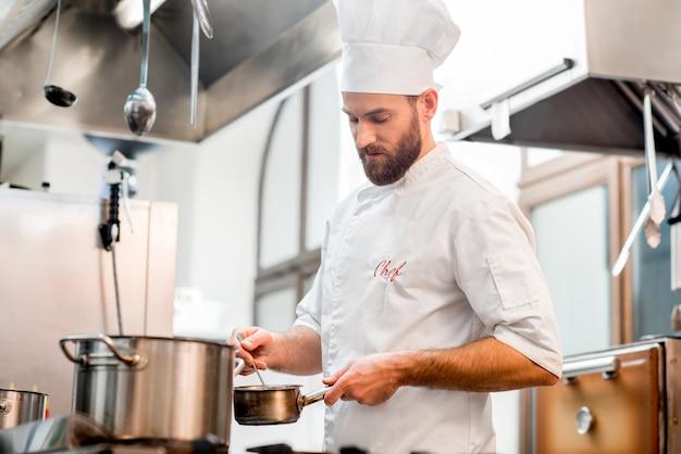 Guapo cocinero cocinero en uniforme cocinando alimentos en la estufa de gas en la cocina del restaurante