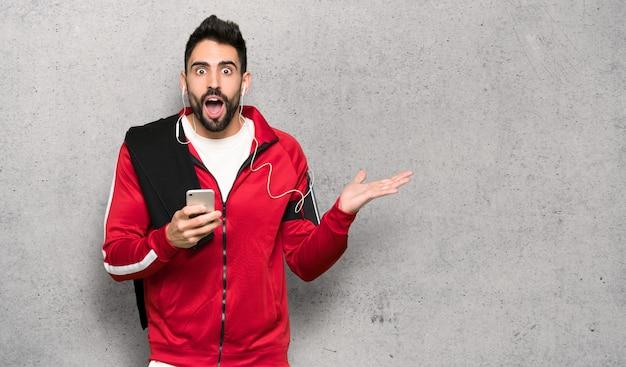 Guapo deportista sorprendido y enviando un mensaje sobre una pared texturizada