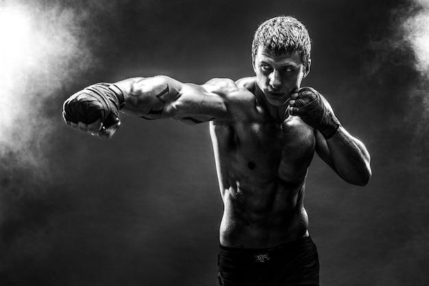 Guapo deportista en topless practicando golpes
