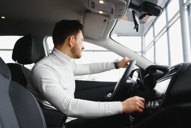 Guapo empresario barbudo está sentado en un coche nuevo en concesionario de coches