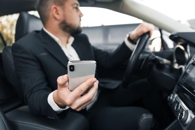 Guapo empresario caucásico conductor dentro del vehículo con gadget y consultar el correo y hablar con socios
