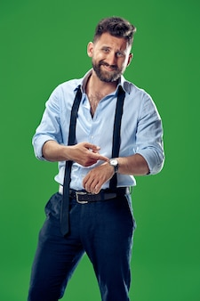 Guapo empresario comprobando su reloj de pulsera aislado en verde