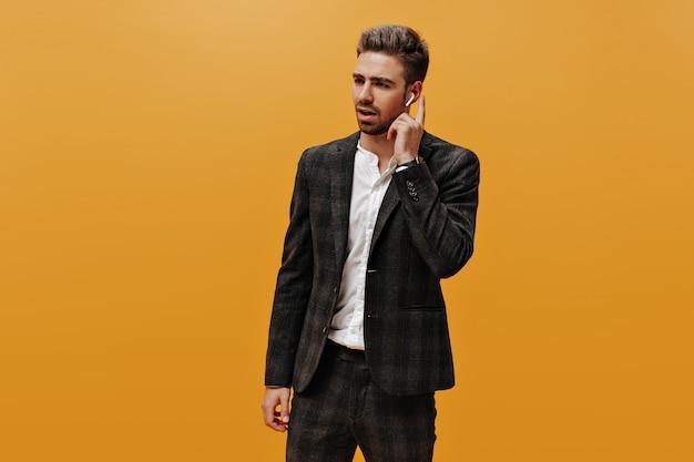 Guapo encantador joven barbudo en traje a cuadros y camisa blanca posa en la pared naranja y toca auriculares inalámbricos.