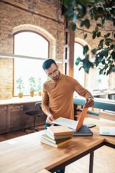 Guapo escritor barbudo. guapo escritor barbudo con gafas de pie en la oficina de impresión espaciosa luz
