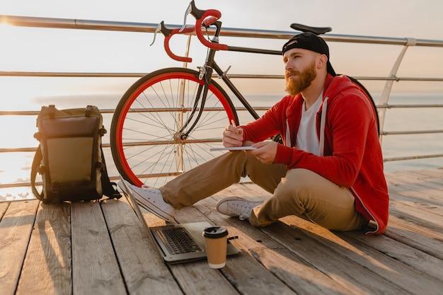 Guapo estilo hipster hombre barbudo que trabaja como autónomo en línea en una computadora portátil con mochila y bicicleta en el amanecer de la mañana junto al mar mochilero de viajero de estilo de vida activo y saludable