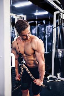 Guapo fisicoculturista musculoso haciendo ejercicio pesado para tríceps