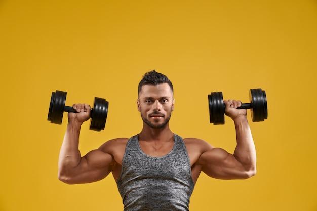 Guapo fisicoculturista trabajando con pesas